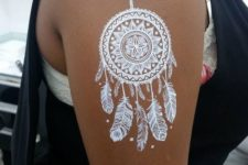 18 white dream catcher with feathers on an arm