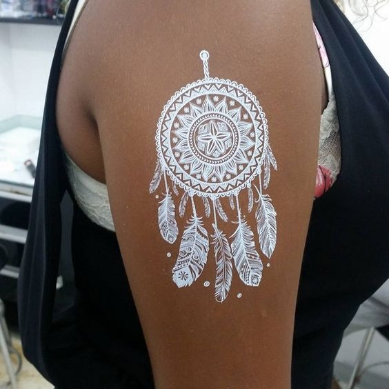 white dream catcher with feathers on an arm