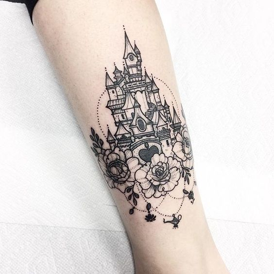 a black ink wrist tattoo with a princess castle and flowers