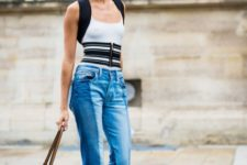 With black and white top, jeans, heels and mini bag