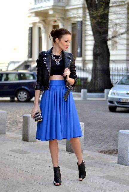 With black crop top, leather jacket, black ankle boots and clutch