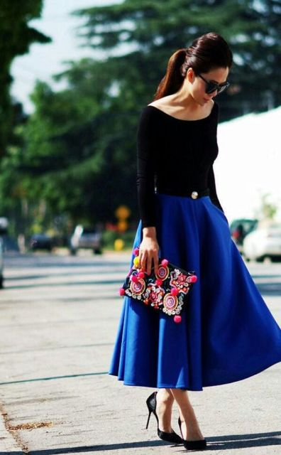 With black shirt, black pumps and colorful clutch