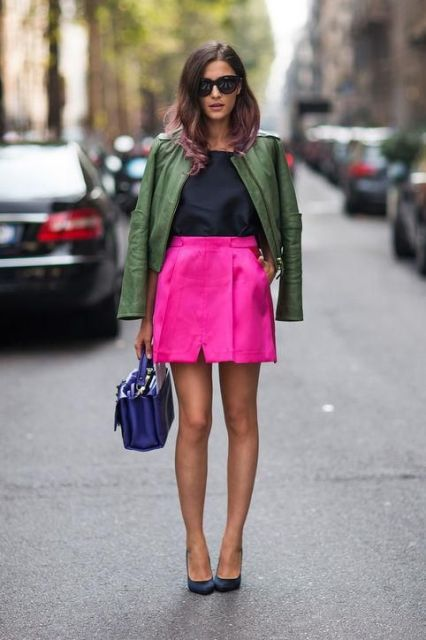 With black shirt, green leather jacket, small bag and dark blue shoes
