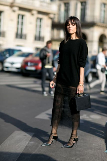 With black sweater, metallic shoes and black small bag