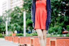 With blue cardigan, orange sneakers and brown backpack