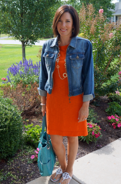 With denim jacket, golden necklace, white sandals and colored bag