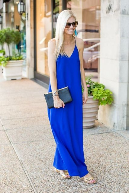 With golden flat sandals, black clutch and oversized sunglasses