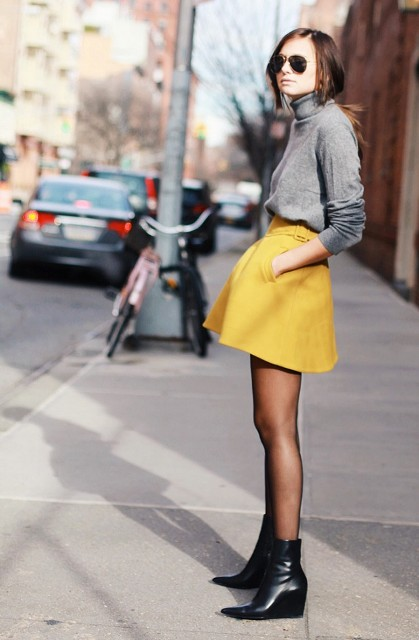 With gray turtleneck and black ankle boots