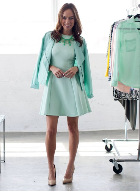 With mint green jacket, green necklace and beige pumps
