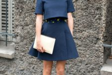 With navy blue crop shirt, skirt and beige clutch