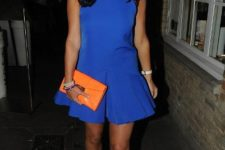 With orange clutch and gray shoes