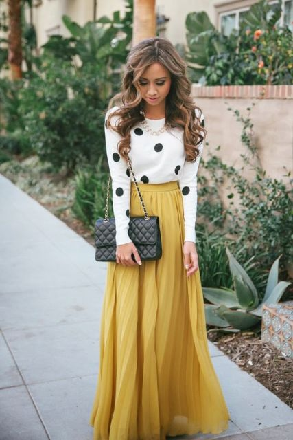 With polka dot shirt and chain strap bag