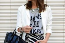 With printed shirt, white blazer and big leather bag