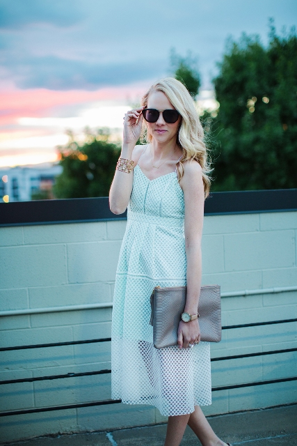 With sunglasses and gray clutch