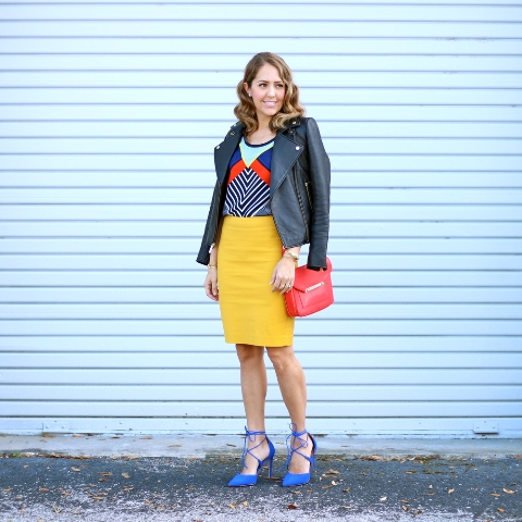 With unique shirt, leather jacket, red bag and blue heels