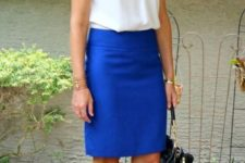 With white shirt, blue necklace and black bag