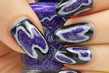 bold geode-inspired manicure in black and purple