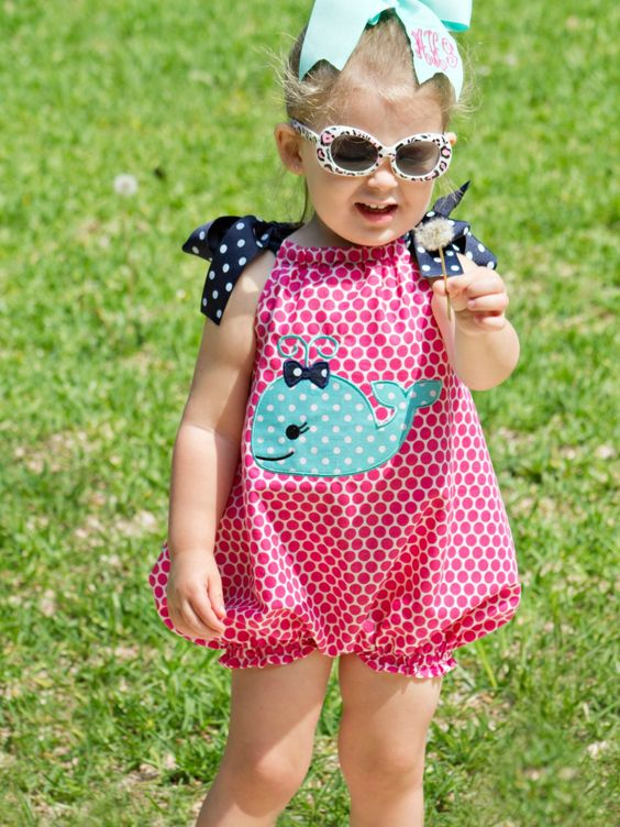 a pink polka dot romper with a whale applique and bows