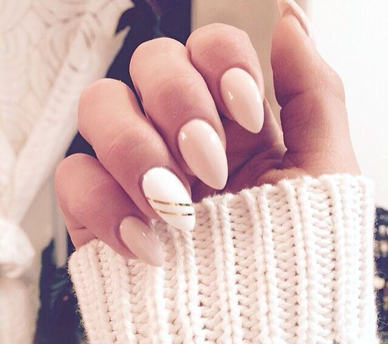 nude nails and an accent white one with two thing gold stripes