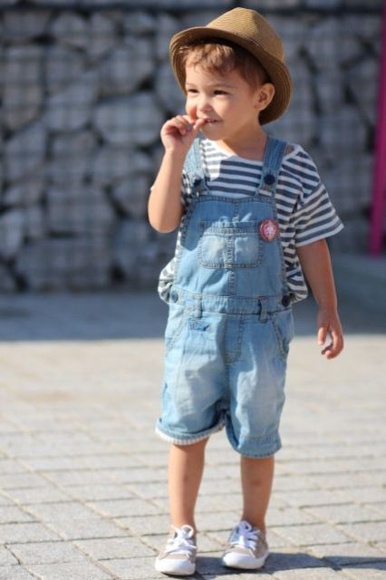 a striped navy and white tee and a light blue denim overall with Converse