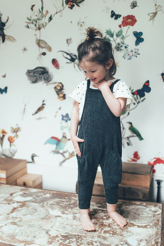a black and white polka dot tee and a black strap overall with pockets
