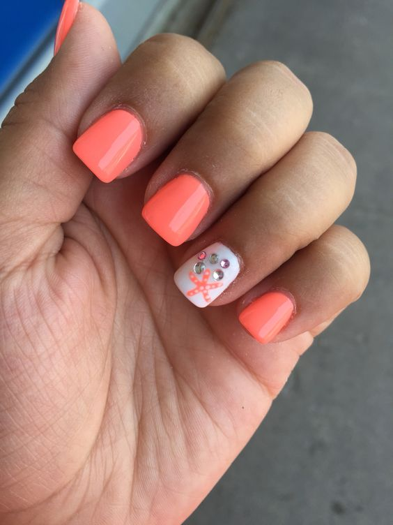 orange nails and an accent one with rhinestones and a starfish