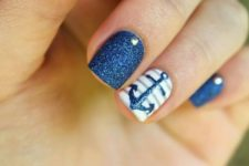 10 navy glitter nails with rhinestones and a striped accent nail with an anchor