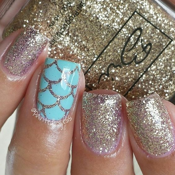 gold glitter nails and an aqua nail with fish scale decor