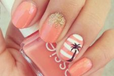12 coral-colored nails with gold glitter and an accent striped nail with a palm tree
