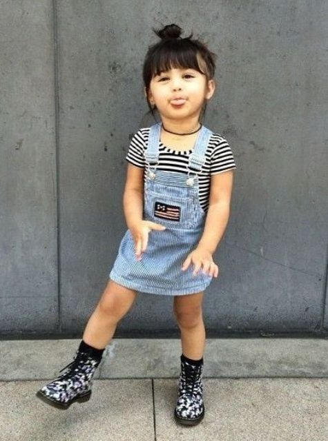 a striped black and white tee and a blue denim overall with boots