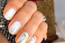 13 white nails with gold glitter imitating sand and palm trees