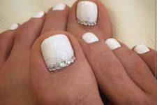 16 white nails with silver glitter and beads on the landing