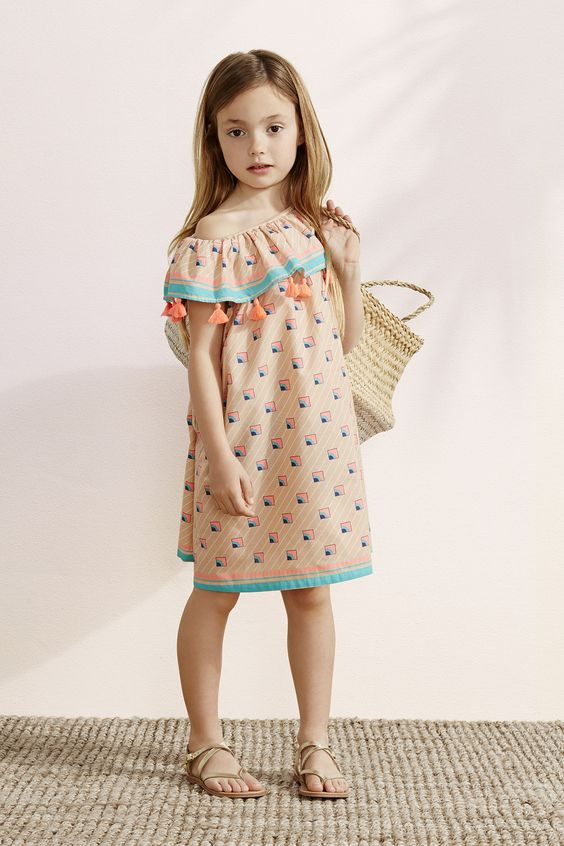 perfect beach outfit with a one shoulder peachy dress with a ruffled top and tassels