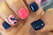 18 royal blue nails, a pink one and a striped glitter one with an anchor