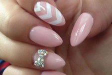 21 pink nails with a chevron one and a rhinestone bow one