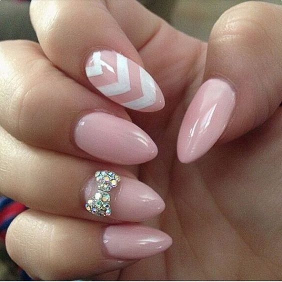 pink nails with a chevron one and a rhinestone bow one