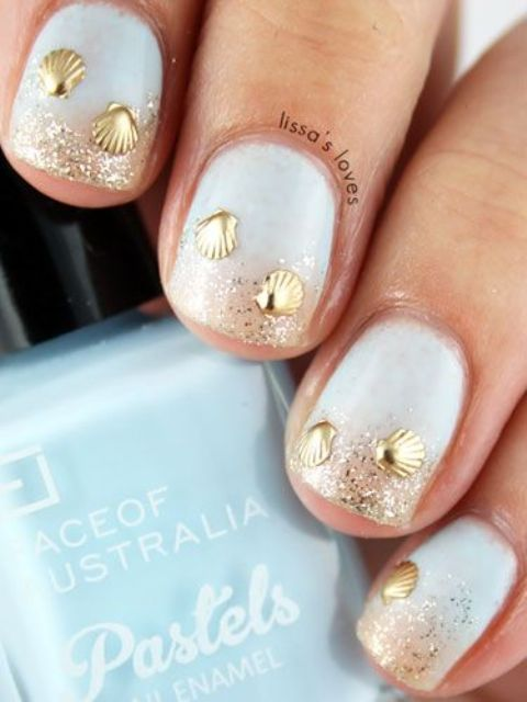 white nails with gold glitter and gold shell decor