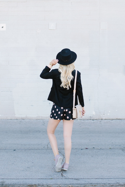 With black jacket, black hat and gray sneakers