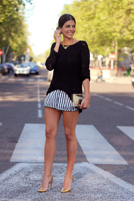 With black loose shirt, golden pumps and clutch