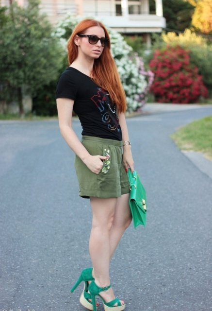 With black t shirt, green sandals and green bag