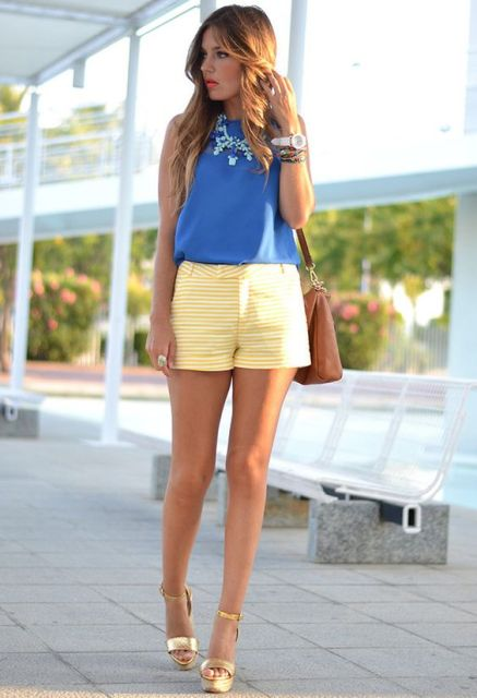 With blue top, brown bag and golden platform sandals
