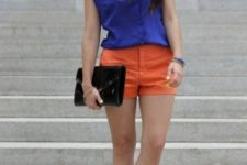 With blue top, printed shoes and black clutch