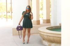 With dark green dress and leather bag