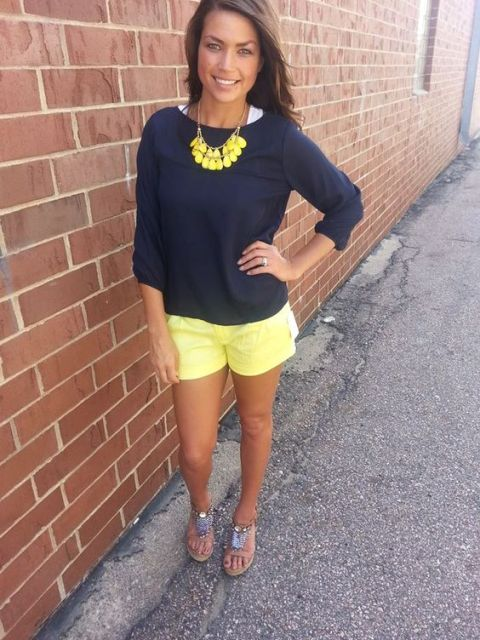 With navy blue shirt, yellow necklace and sandals