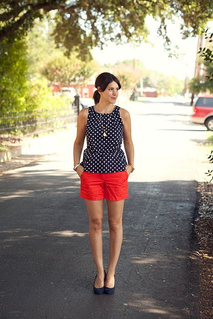 With polka dot blouse and navy blue flats
