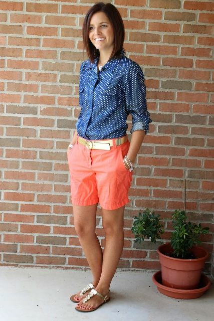 Cool summer work outfit with orange shorts, polka dot shirt, golden belt and metallic sandals