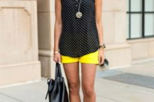 With polka dot top, red sandals and black bag