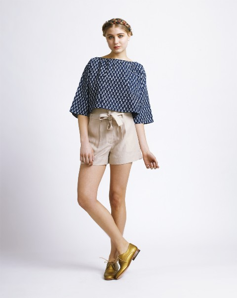 Beige shorts with printed blouse and golden shoes
