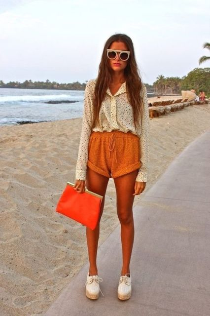 With printed shirt, white shoes, orange clutch and sunglasses