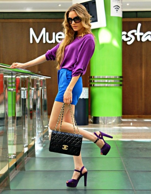 With purple blouse, purple heels and black bag